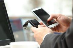 同步一个巧妙的手表和电话的商人 免版税库存图片