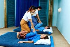 同步做泰国按摩的两个泰国女按摩师 免版税图库摄影