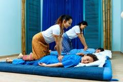 同步做泰国按摩的两个泰国女按摩师 免版税库存图片