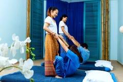同步做泰国按摩的两个泰国女按摩师 图库摄影