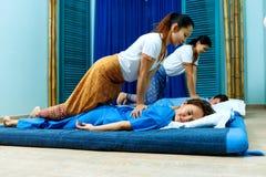 同步做泰国按摩的两个泰国女按摩师 库存图片