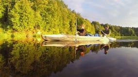 同步用浆划独木舟的男人和妇女在美丽的河 股票录像