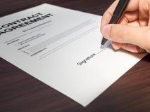 同笔宏指令的手签署的合同 库存图片