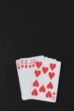 同花大顺在黑背景的纸牌游戏手,纸牌,您的copyspace营销文本 免版税库存照片