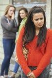 同辈说闲话的不快乐的十几岁的女孩 库存照片