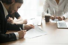 同div的满意的微笑的商人签署的企业合同 免版税库存图片