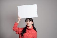 20名亚裔妇女演播室画象使拿着广告牌惊奇 库存图片
