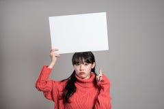 20名亚裔妇女演播室画象使拿着广告牌惊奇 库存照片