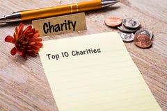 名列前茅在笔记本和木板的10个慈善机构概念 免版税库存图片