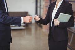 给名片的女实业家客户在办公室 免版税库存图片