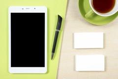 名片空白、智能手机或片剂个人计算机、咖啡杯和笔在办公桌台式视图 公司文具 免版税库存图片