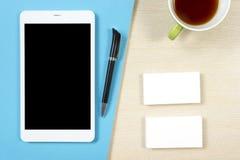 名片空白、智能手机或片剂个人计算机、咖啡杯和笔在办公桌台式视图 公司文具 图库摄影
