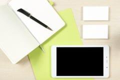 名片空白、智能手机或片剂个人计算机、笔记薄和笔在办公桌台式视图 公司文具 库存照片