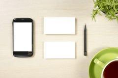 名片空白、智能手机或片剂个人计算机、花、咖啡杯和铅笔在办公桌台式视图 总公司 免版税库存照片