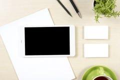 名片空白、智能手机或片剂个人计算机、花、咖啡杯和铅笔在办公桌台式视图 总公司 图库摄影