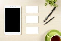 名片空白、智能手机或片剂个人计算机、花、咖啡杯和铅笔在办公桌台式视图 总公司 库存图片