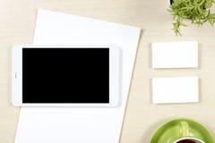 名片空白、智能手机或片剂个人计算机、花和咖啡杯在办公桌台式视图 公司文具 免版税库存图片