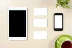 名片空白、智能手机或片剂个人计算机、花和咖啡杯在办公桌台式视图 公司文具 库存照片