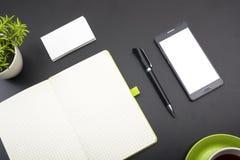 名片空白、智能手机或片剂个人计算机、花和笔在办公桌台式视图 公司文具 免版税库存图片