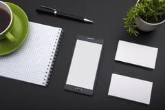 名片空白、智能手机或片剂个人计算机、花和笔在办公桌台式视图 公司文具 免版税库存照片