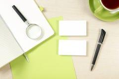 名片空白、笔记薄、咖啡杯和笔在办公桌台式视图 公司文具烙记的大模型 库存图片