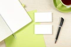 名片空白、笔记薄、咖啡杯和笔在办公桌台式视图 公司文具烙记的大模型 免版税图库摄影
