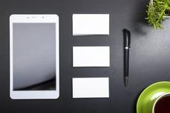 名片空白、笔记薄、咖啡杯和笔,在办公桌台式视图的花 公司文具烙记 库存照片