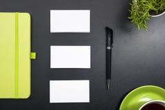 名片空白、笔记薄、咖啡杯和笔,在办公桌台式视图的花 公司文具烙记 免版税图库摄影