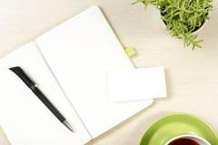 名片空白、笔记薄、咖啡杯和笔,在办公桌台式视图的花 公司文具烙记 免版税库存照片