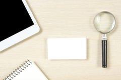 名片空白、笔记薄、智能手机或者片剂个人计算机,在办公桌台式视图的放大镜 总公司 图库摄影
