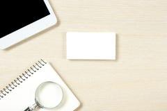 名片空白、笔记薄、智能手机或者片剂个人计算机,在办公桌台式视图的放大镜 总公司 库存照片
