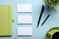 名片空白、笔记薄、花、咖啡杯和笔在办公桌台式视图 公司文具烙记 免版税库存照片