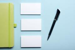 名片空白、笔记薄、花、咖啡杯和笔在办公桌台式视图 公司文具烙记 免版税库存图片
