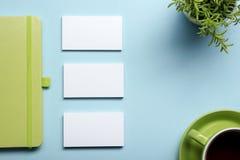 名片空白、笔记薄、花、咖啡杯和笔在办公桌台式视图 公司文具烙记 库存照片