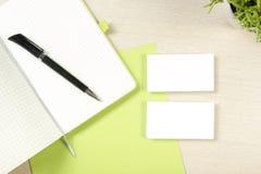 名片空白、笔记薄、花和笔在办公桌台式视图 公司文具烙记的大模型 免版税库存照片