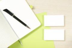 名片空白、笔记薄和笔在办公桌台式视图 公司文具烙记的大模型 免版税库存图片