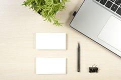 名片空白、膝上型计算机、花和铅笔在办公桌台式视图 公司文具烙记的大模型 免版税库存照片