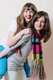 2名年轻令人愉快的俏丽的妇女有乐趣友好的拥抱的和乘坐的愉快的微笑的&看的照相机 免版税库存图片