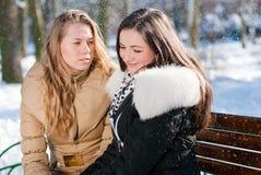 2名年轻美丽的迷人的妇女坐一条长凳在冬天停放户外 免版税库存照片