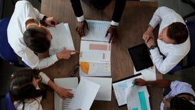 后不同的国籍的创造性的经理办公室队做大书桌的顶视图在 影视素材