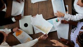 后不同的国籍的创造性的经理办公室队做大书桌的顶视图在 股票录像