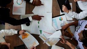 后不同的国籍的创造性的经理办公室队做大书桌的顶视图在 股票视频