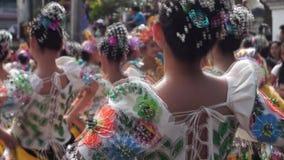 后侧方接近文化舞蹈家在各种各样的椰子服装舞蹈沿庆祝受护神的街道 影视素材