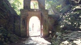 后侧方视图妇女通过在石曲拱的门走 影视素材