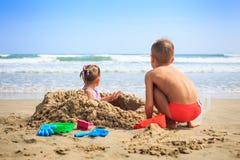 后侧方视图小女孩男孩由沙子堆坐海滩 免版税图库摄影
