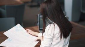 后侧方视图,女孩自由职业者看在咖啡馆,在桌,慢动作上的膝上型计算机的菜单 股票录像