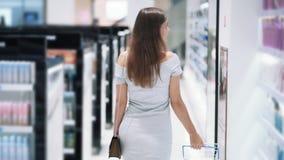 后侧方视图,女孩购物在有篮子的化妆用品商店,慢动作 影视素材