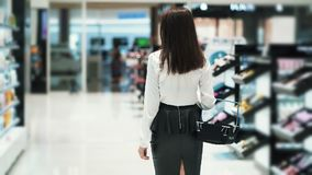 后侧方视图,女孩购物在有篮子的化妆用品商店,慢动作 股票录像