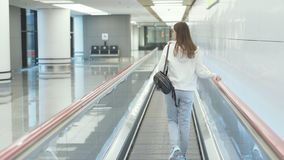 后侧方运动服的视图妇女有背包的在移动的走道努力去做在机场 影视素材