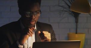 后努力研究他的膝上型计算机的疲乏的年轻商人在晚上 坐在书桌的困人在黑暗的办公室 他推迟 股票视频
